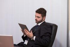 Бизнесмен на проломе с его компьютером Стоковые Изображения