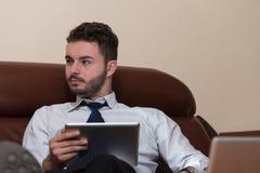 Бизнесмен на проломе с его компьютером Стоковое Фото