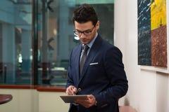 Бизнесмен на проломе с его сенсорной панелью Стоковые Изображения
