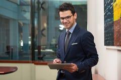 Бизнесмен на проломе с его сенсорной панелью Стоковое Изображение