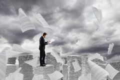 Бизнесмен на работе над кучей бумажных башен рабочих листов стоковая фотография