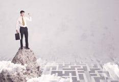 Бизнесмен на скале над лабиринтом Стоковое Изображение RF