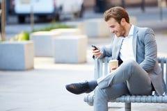 Бизнесмен на скамейке в парке с кофе используя мобильный телефон