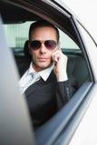 Бизнесмен на солнечных очках телефона нося Стоковые Фото