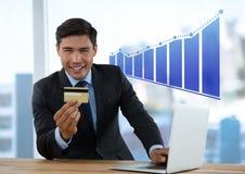 Бизнесмен на столе с инкрементировать компьтер-книжки и карточки и диаграммы в виде вертикальных полос банка Стоковые Изображения