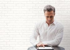 Бизнесмен на столе смотря таблетку против белой стены Стоковые Фото