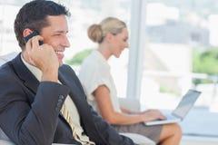 Бизнесмен на телефоне при его коллега работая на компьютере Стоковая Фотография