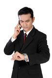 Бизнесмен на телефоне проверяя на его вахте, изолированном на белизне стоковое фото rf