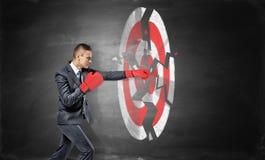 Бизнесмен носит перчатки бокса и ломает чертеж мела круглой цели archery Стоковая Фотография RF