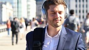 Бизнесмен нося беспроволочные наушники идя для работы сток-видео