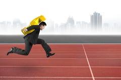 Бизнесмен нося золотой знак доллара бежать на следе Стоковые Фото