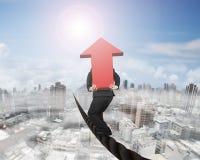 Бизнесмен нося красный знак стрелки 3D балансируя на проводе Стоковое Изображение
