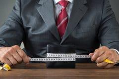 Бизнесмен оборачивая бумажник с измеряя лентой Стоковое Изображение