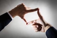 Бизнесмен обрамляя его руки на пустой бетонной стене Стоковое Фото