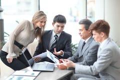 Бизнесмен обсуждая с рабочими документами команды дела стоковые фото