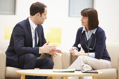 Бизнесмен обсуждая доктора женщины результатов теста Стоковая Фотография