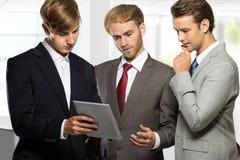 Бизнесмен 3 обсуждая планы на офисе Стоковое Фото