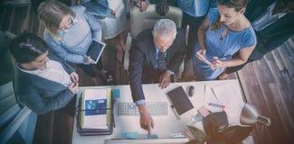 Бизнесмен обсуждая с коллегами над компьютером Стоковое фото RF