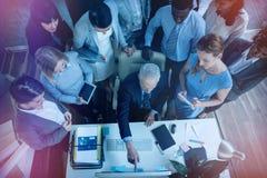 Бизнесмен обсуждая с коллегами над компьютером Стоковая Фотография