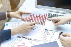 Бизнесмен 2 обсуждая финансовую диаграмму с таблеткой и компьтер-книжкой в внешнем саде парка Стоковая Фотография RF