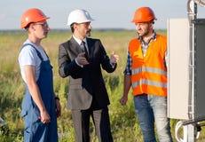 Бизнесмен объясняя работая процесс панелей солнечных батарей к работникам Стоковое Изображение RF