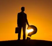 Бизнесмен освещенный задней частью держа знак вопросов Стоковые Фото