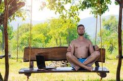 Бизнесмен ослабляет после работы на компьтер-книжке сидя в pos лотоса Стоковые Фотографии RF