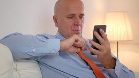 Бизнесмен ослабляя в финансовых новостях мобильного телефона пользы офиса читая на интернете видеоматериал