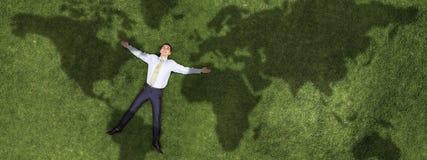 Бизнесмен ослабляя на траве стоковая фотография