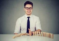 Бизнесмен останавливая эффект домино стоковое изображение