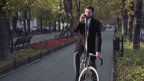 Бизнесмен остановил его велосипед для того чтобы поговорить на телефоне сток-видео