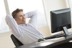 Бизнесмен ослабляя пока смотрящ настольный ПК стоковое фото