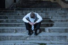 Бизнесмен отжал и потерял сидеть снаружи после терять его работу стоковое изображение