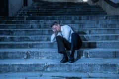 Бизнесмен отжал и потерял сидеть снаружи после терять его работу стоковая фотография rf