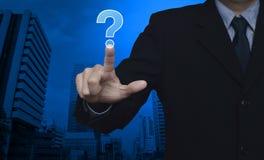 Бизнесмен отжимая значок знака вопросительного знака над bac башни города Стоковые Фото