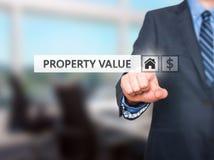 Бизнесмен отжимая кнопку стоимости имущества на виртуальных экранах стоковые фотографии rf