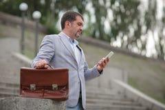 Бизнесмен отправляя СМС с телефоном Директор с портфелем на запачканной предпосылке Концепция профессионализма скопируйте космос Стоковое фото RF