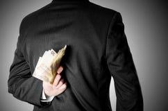 Бизнесмен одетый в костюме пряча 50 бумажных денег евро Стоковая Фотография