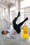 Бизнесмен падая на влажный пол стоковая фотография