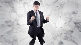Бизнесмен перед белыми документами предпосылки и летания Стоковое Изображение