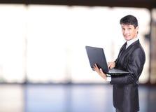 Бизнесмен перед портативным компьютером Стоковые Изображения