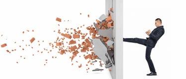 Бизнесмен пиная крепко стену и задавливает его Стоковые Изображения RF
