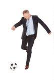 Бизнесмен пиная футбольный мяч Стоковая Фотография RF