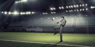Бизнесмен пиная шарик стоковые фото