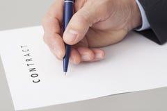 Бизнесмен писать контракт Стоковые Фотографии RF