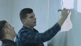 Бизнесмен писать функцию и кладя его идеи на белую доску во время представления Публикация идей дела и сток-видео