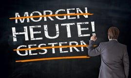 Бизнесмен пишет в немце сегодня, вчера, завтра на черноте Стоковое Изображение RF