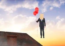 Бизнесмен плавая с воздушными шарами и сумкой на голове над крышей Стоковые Фото