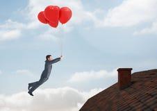 Бизнесмен плавая с воздушными шарами крышей с печной трубой и голубым небом Стоковая Фотография RF