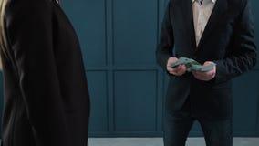 Бизнесмен подсчитывая банкноты доллара Коммерческая сделка с переходом денег Конец-вверх человека дает стог  сток-видео